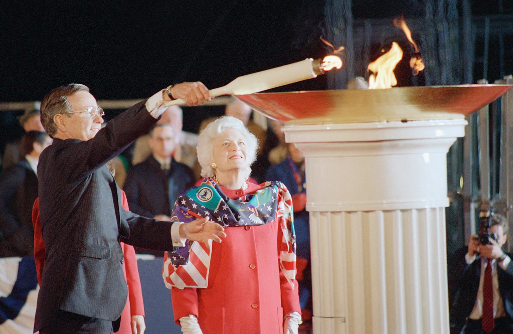 . President-elect George Bush lights a torch during opening inaugural ceremonies at the Lincoln Memorial, Wednesday, Jan. 18, 1989 in Washington as Wife Barbara looks on. (AP Photo/Rick Bowmer)