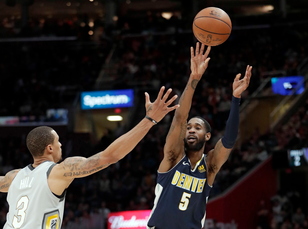 . Denver Nuggets\' Will Barton (5) passes over Cleveland Cavaliers\' George Hill (3) in the second half of an NBA basketball game, Saturday, March 3, 2018, in Cleveland. The Nuggets won 126-117. (AP Photo/Tony Dejak)