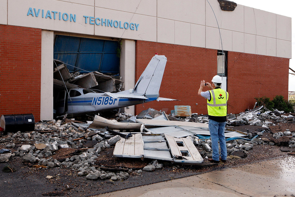 . Cary Dehart photographs tornado damage at Canadian Valley Technology Center\'s Aviation Technology building in El Reno, Oklahoma June 1, 2013. Nine people were killed in tornadoes that swept through central Oklahoma on Friday, part of a storm system that caused widespread flooding in Oklahoma City and its suburbs, the state\'s chief medical examiner said on Saturday. REUTERS/Bill Waugh