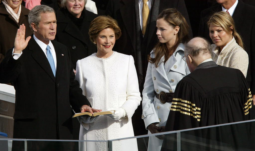 . President Bush takes the oath of office from Chief Justice William Rehnquist, right, with first lady Laura Bush, and his daughters Barbara and Jenna at his side at the US Capitol in Washington, Jan. 20, 2005. In background are Speaker of the House Dennis Hastert, left, and Sen. Trent Lott, R-Miss. (AP Photo/Paul Sancya)