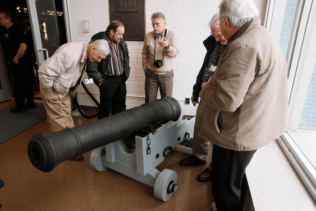 . Visitors view a 18th century British cannon that was found in the Detroit River in 2011 while on display, following a three-year restoration, at the Dossin Great Lakes Museum in Detroit Wednesday, Dec. 10, 2014. (AP Photo/Paul Sancya)
