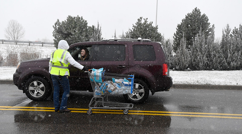 A Walmart employee talks to a motorist as she hands out water, candy, and cookies to motorists stuck in the traffic in the parking lot in Timnath, Colo. on Monday, Nov. 25, 2019.