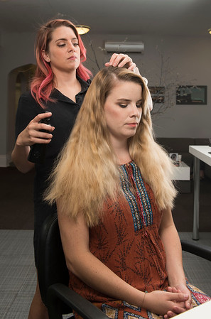 DAVID LIPNOWSKI / WINNIPEG FREE PRESS  Britney Robson uses Oribe products to tame frizzy and sun dried hair on model Raechel Warde at Edward Carrier salon Thursday July 21, 2016.