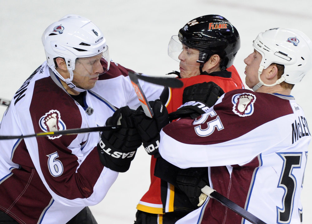 . Calgary Flames\' Jiri Hudler (C) is sandwiched by Colorado Avalanche\'s Erik Johnson (L) and Cody McLeod during the first period of their NHL hockey game in Calgary, Alberta, March 27, 2013. REUTERS/Mike Sturk