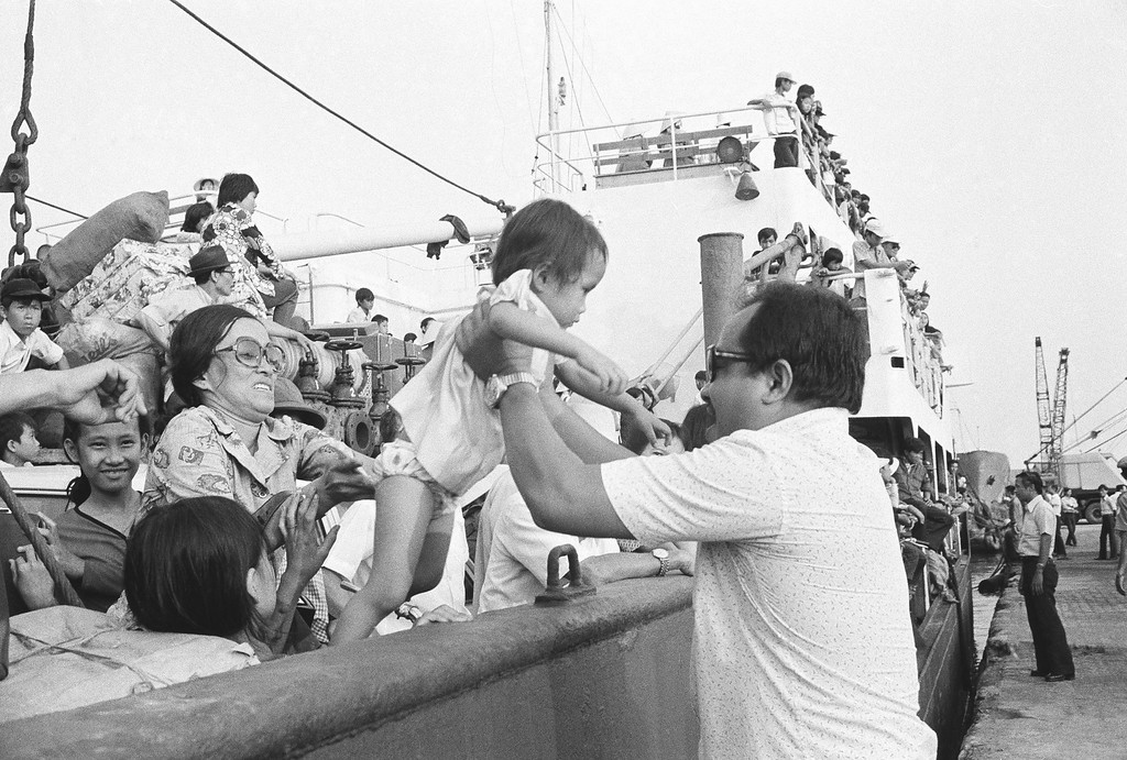 . Father and mother, from front and back, help lift their youngster from ship to dock as the family and hundreds of other refugees arrive at Saigon dock, Friday, March 29, 1975. The arrival of the merchant vessel was one of the first at the capital since the mass exodus of South Vietnamese from the central highlands and Northern provinces. (AP Photo/Phuoc)