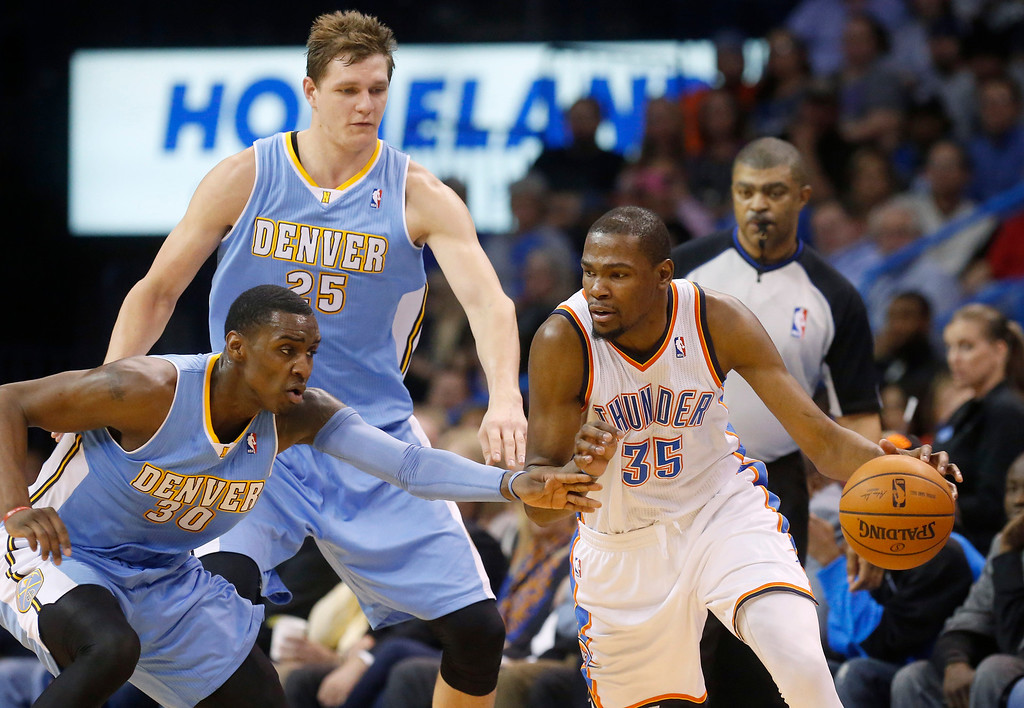 . Oklahoma City Thunder forward Kevin Durant (35) drives past Denver Nuggets forward Quincy Miller (30) and center Timofey Mozqov (25) in the second quarter of an NBA basketball game in Oklahoma City, Monday, March 24, 2014. Oklahoma City won 117-96. (AP Photo/Sue Ogrocki)