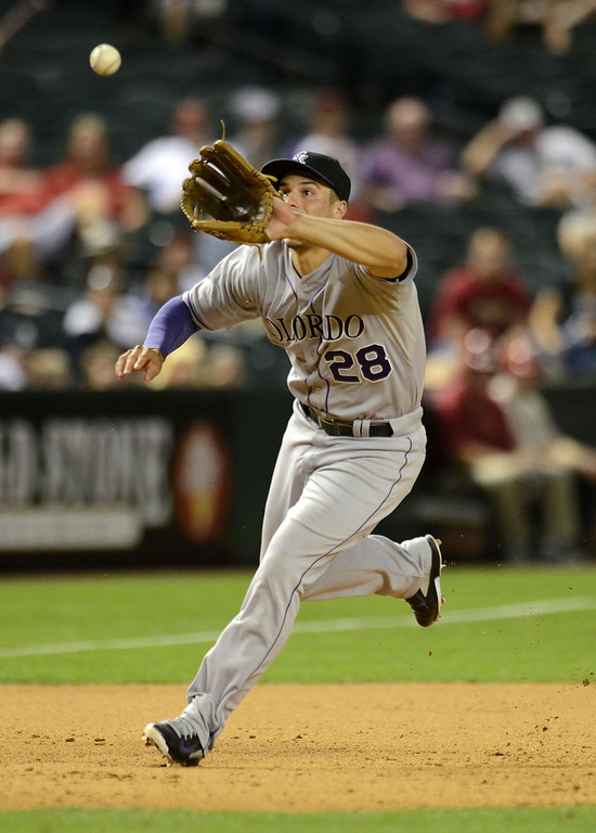 . Nolan Arenado #28 of the Colorado Rockies makes a running play on a ground ball against the Arizona Diamondbacks in the eighth inning at Chase Field on April 28, 2014 in Phoenix, Arizona. Colorado won 8-5. (Photo by Norm Hall/Getty Images)