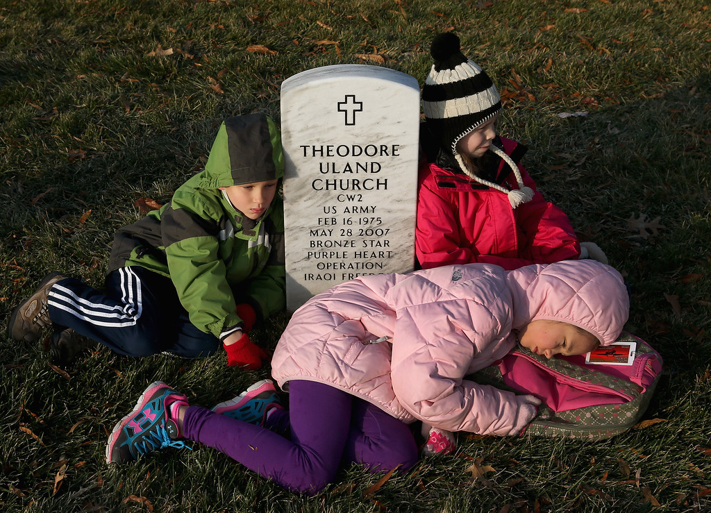 . 7yo Jack Harris (L), 9yo Jada Harris (C) and 7yo Olivia Bernhardy sit at the grave of a close family friend during the National Wreaths Across America Day at Arlington National Cemetery, December 13, 2014 in Arlington, Virginia. Volunteers placed wreaths throughout the entire cemetery in honor of Arlington\'s 150th anniversary. .  (Photo by Mark Wilson/Getty Images)
