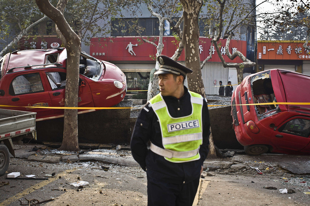 . Damaged vehicles lie near the blast site after an oil pipeline exploded, ripping roads apart, turning cars over and sending thick black smoke billowing over the city of Qingdao, east China\'s Shandong province on November 22, 2013, killing 35 people, authorities said, in the latest deadly industrial accident in the country.      AFP PHOTOSTR/AFP/Getty Images