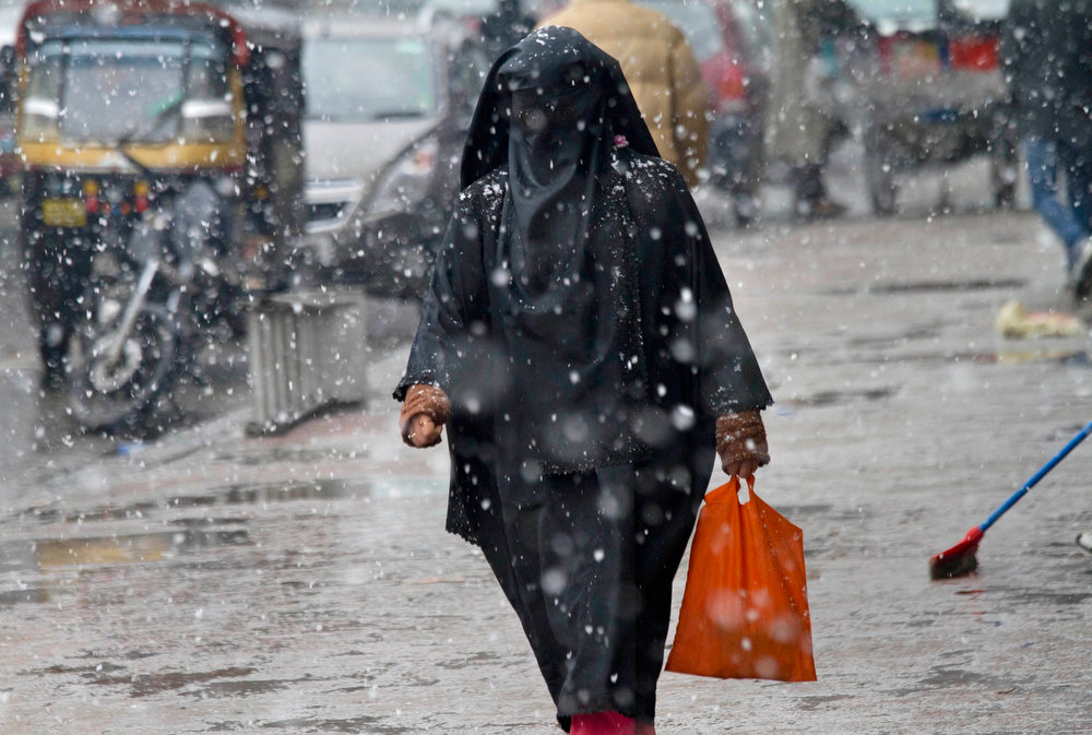 Description of . A Kashmiri woman walks as snow falls in Srinagar, India, Saturday, Jan. 12, 2013. Traffic on the 300 kilometers (188 miles) long Jammu-Srinagar national highway was suspended due to heavy snowfall, according to news reports. (AP Photo/Dar Yasin)