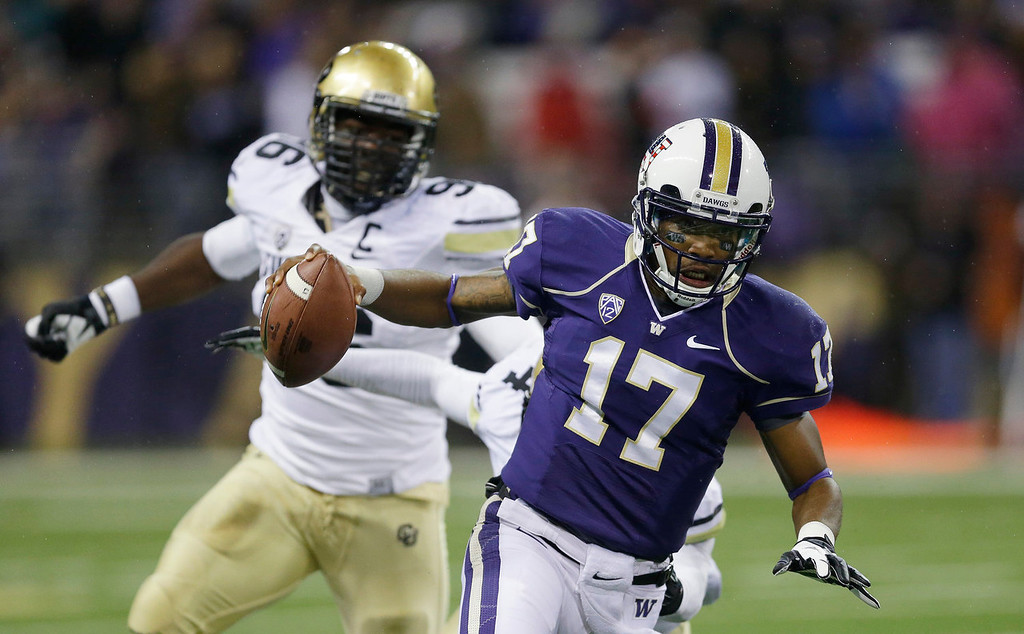 . Washington quarterback Keith Price (17) scrambles away from Colorado defensive lineman Chidera Uzo-Diribe, left, in the first half of an NCAA college football game on Saturday, Nov. 9, 2013, in Seattle. (AP Photo/Ted S. Warren)