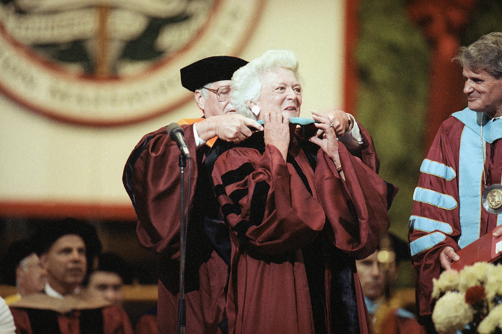 . First Lady Barbara Bush, center, has a doctorates hood placed over her shoulders during Northeastern Universitys spring commencement, Saturday, June 15, 1991, Boston, Mass. Bush was the commencement speaker and recipient of an honorary doctorate for public service. Placing the hood over her shoulders is Northeastern University Trustee Dennis Placard. (AP Photo/Stephan Savola)
