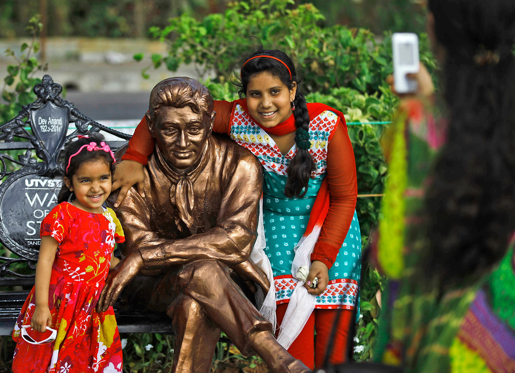 """. In this April 18, 2013 photo, Indian children pose for photographs with a statue of late Bollywood star Dev Anand in Mumbai, India. Friday, May 3 marks exactly a hundred years after India\'s first feature film \""""Raja Harischandra,\"""" a silent movie, was screened in 1913. India produced almost 1,500 movies last year and the industry is expected to grow from $ 2 billion to $ 3.6 billion in the next five years, according to consultancy KPMG. (AP Photo/Rafiq Maqbool)"""