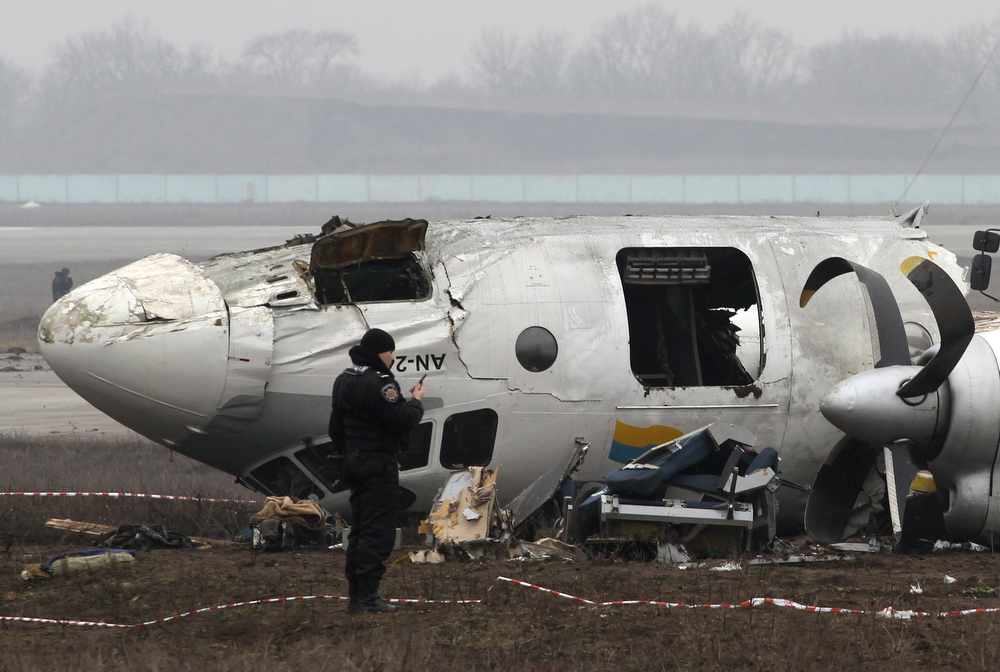 Description of . A general view of a damaged twin-engined Antonov turboprop plane, which broke up during an emergency landing the day before, is seen near the landing strip of the airport in Donetsk, February 14, 2013. At least five people were killed when a plane carrying supporters to a European soccer match in eastern Ukraine overshot the runway and broke up when it attempted an emergency landing late on Wednesday, officials said. The twin-engined Antonov turboprop was bringing 45 passengers and crew on a charter flight from the Black Sea coastal city of Odessa to Donetsk - most of them fans looking forward to attending a Champions League clash between the Ukrainian home team Shakhtar and Germany's Borussia Dortmund. REUTERS/Stringer