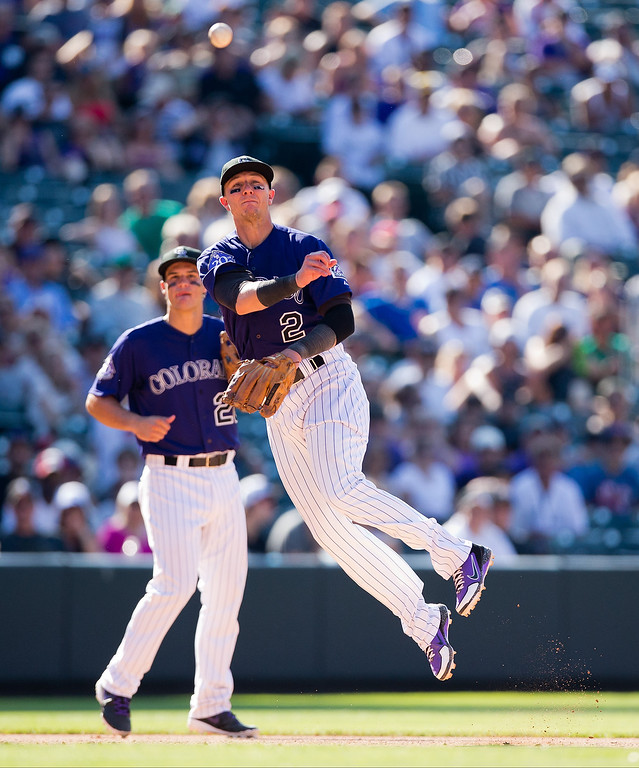 . Shortstop Troy Tulowitzki #2 of the Colorado Rockies makes a throw on the run for the second out of the ninth inning as third baseman Nolan Arenado #28 looks on against the Chicago Cubs at Coors Field on July 21, 2013 in Denver, Colorado. The Rockies defeated the Cubs 4-3.  (Photo by Justin Edmonds/Getty Images)