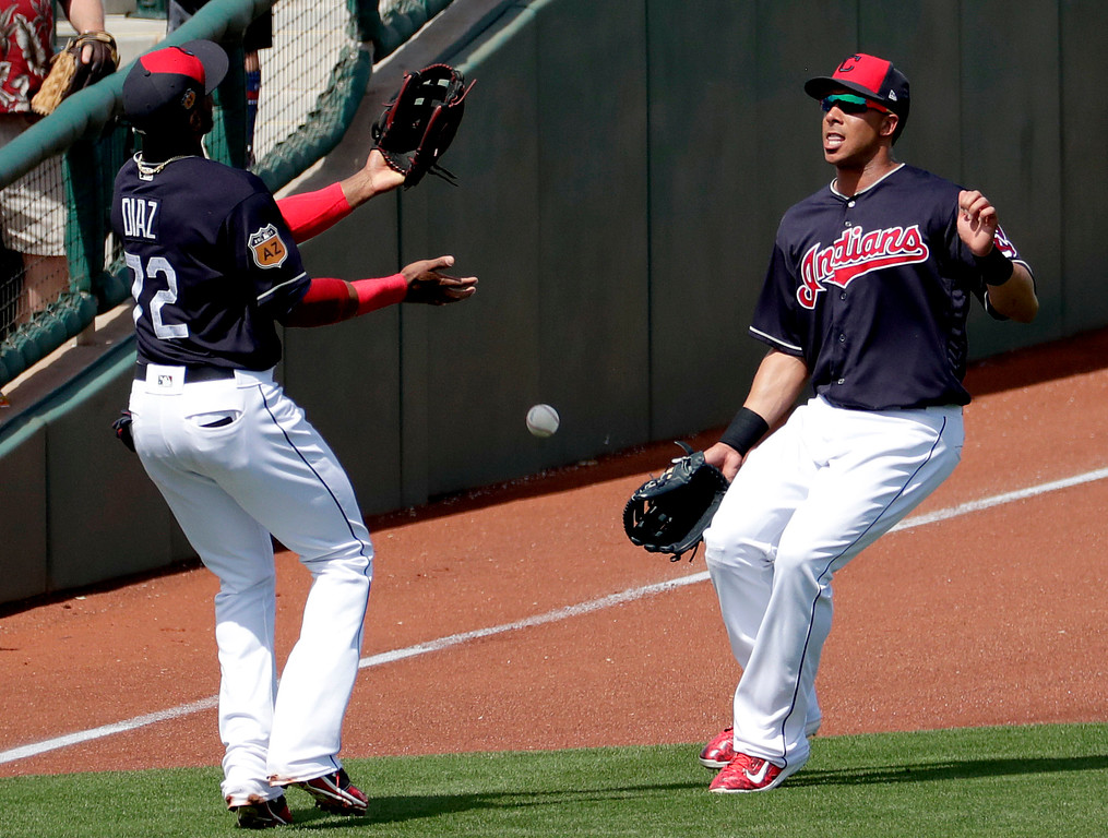 . Cleveland Indians\' Yandy Diaz (72) and Michael Brantley can\'t make the catch on a base hit by Los Angeles Dodgers\' Chase Utley during the first inning of a spring training baseball game, Monday, March 20, 2017, in Goodyear, Ariz. (AP Photo/Matt York)