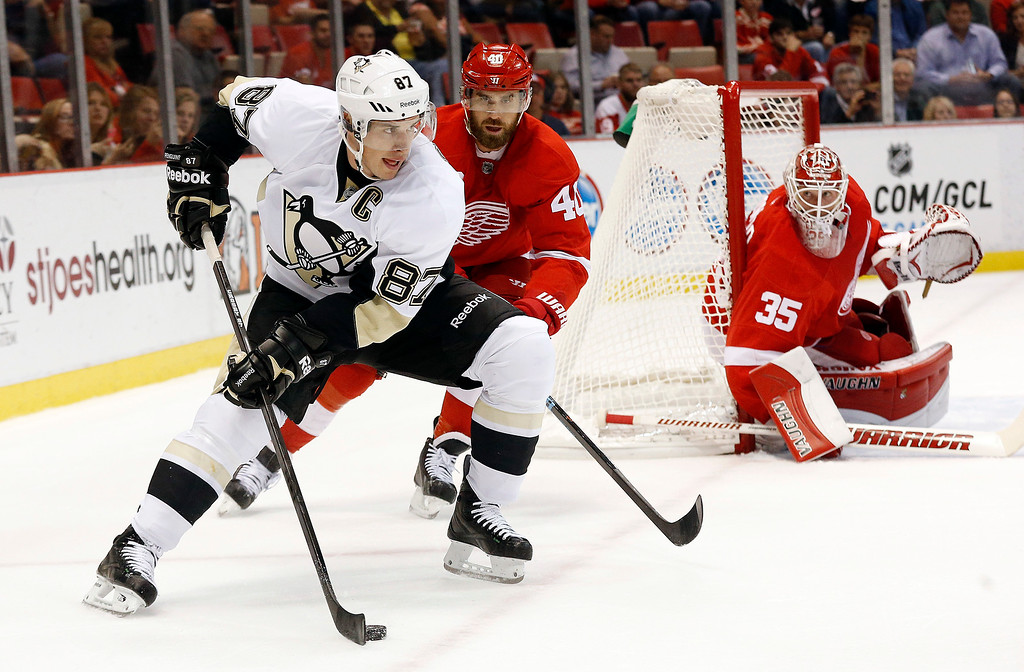 . Pittsburgh Penguins center Sidney Crosby (87) looks to pass as Detroit Red Wings\' Henrik Zetterberg (40), of Sweden, defends in the first period of a NHL preseason hockey game in Detroit Wednesday, Oct. 1, 2014. (AP Photo/Paul Sancya)
