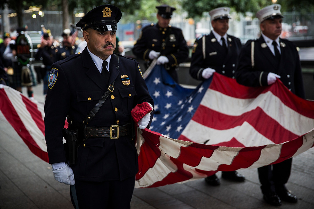 . Members of the New York Police Department, Fire Department of New York and Port Authority of New York and New Jersey Police Department carry an American flag at the beginning of the memorial observances on the 13th anniversary of the Sept. 11 terror attacks on the World Trade Center in New York, Thursday, Sept. 11, 2014.  (AP Photo/Andrew Burton, Pool)
