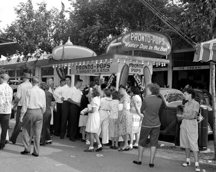 """. \""""Brede Inc. Pronto Pups\"""". People line up to buy Pronto Pups, the first food on a stick at the Minnesota State Fair, when they were introduced in 1947. Photo courtesy of the Minnesota State Fair."""