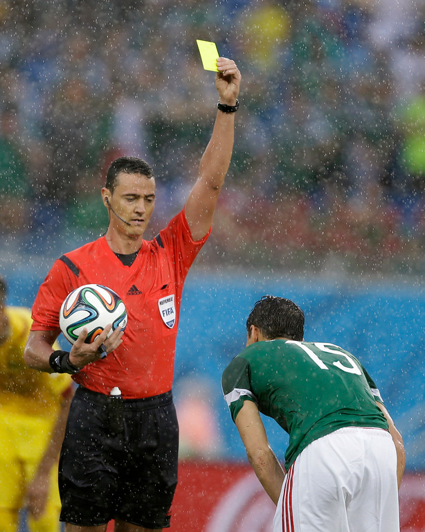 . Wilmar Roldan from Colombia gives a yellow card to Mexico\'s Hector Moreno during the group A World Cup soccer match between Mexico and Cameroon in the Arena das Dunas in Natal, Brazil, Friday, June 13, 2014.  (AP Photo/Ricardo Mazalan)