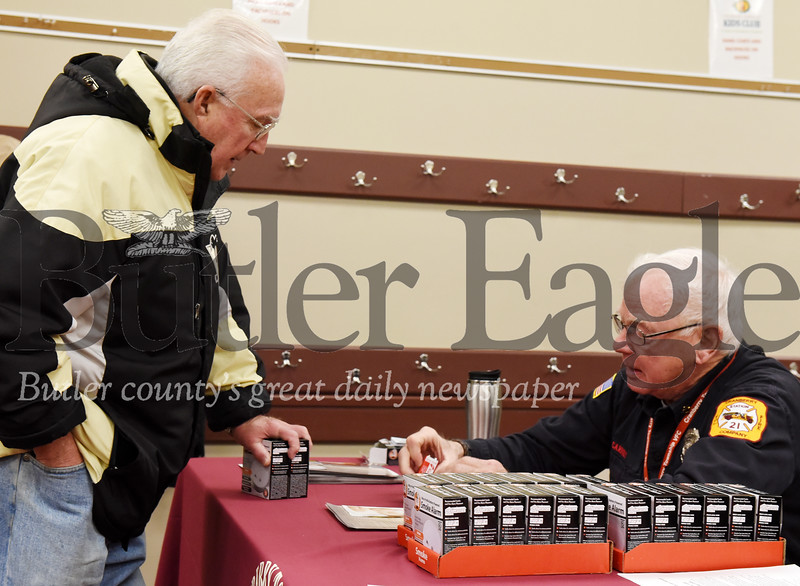 Harold Aughton/Butler Eagle: Jack Carney, right, a Cranberry Township Volunteer Fireman, discusses the importance of senior of replacing their fire detectors with Cranberry resident, Jim Ofriel, Wednesday, Dec. 11, 2019. The CTVF Company handed out free fire detectors to senior citizens of Cranberry Twp. at the Municipal Center. The department raised $3,000 to purchase 700 fire detectors at a discounted cost from Home Depot.