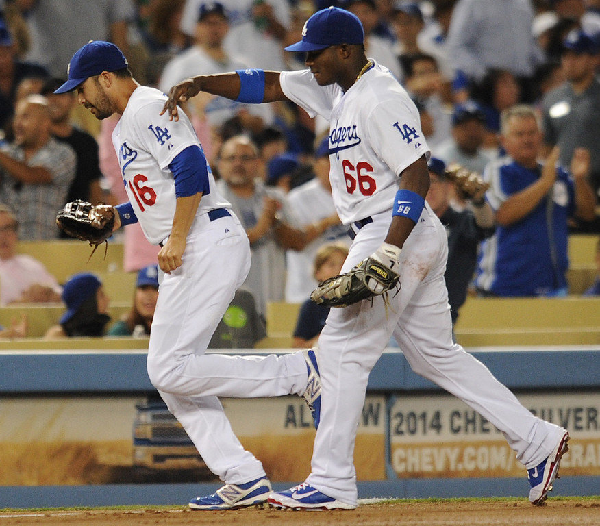 . Dodgers Andre Ethier gets a pat on the back from Yasiel Puig after Ethier made a catch in deep center field to end the 2nd inning. The Cubs were in town to play the Dodgers. Los Angeles, CA. 8/24/2013(John McCoy/LA Daily News)