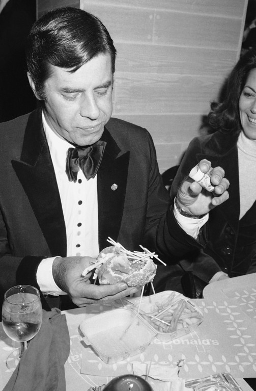 . Jerry Lewis looks at this sandwich after dumping matches on it at the muscular dystrophy $100-a-plate-benefit at the McDonald\'s on Fifth Avenue in New York on Wednesday, Nov. 10, 1976.    Lewis had thought he was putting salt on his sandwich, but had mistakenly picked up a match container. (AP Photo/Ron Frehm)