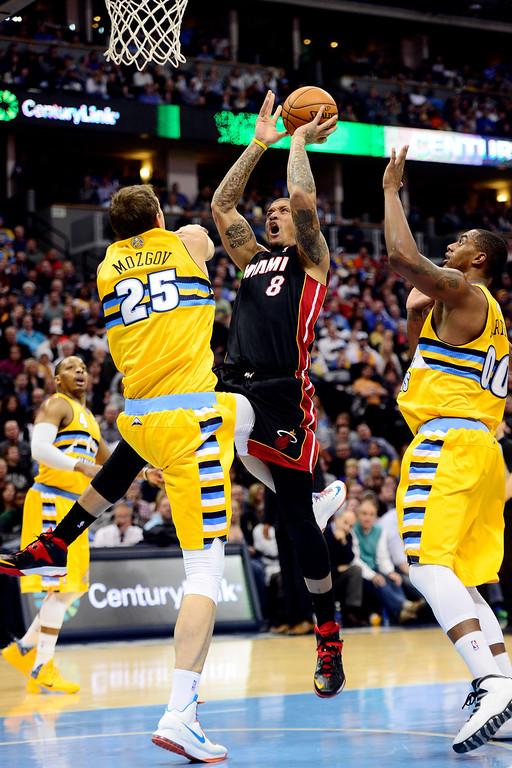 . Michael Beasley (8) of the Miami Heat drives on Timofey Mozgov (25) of the Denver Nuggets and Darrell Arthur (00) during the second half of Miami\'s 97-94 win.   (Photo by AAron Ontiveroz/The Denver Post)