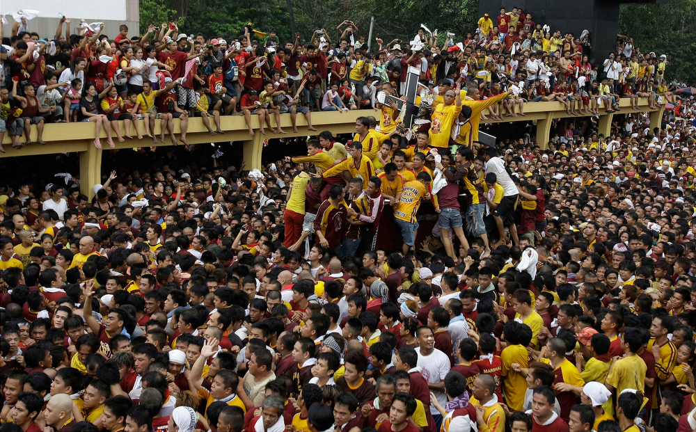 . The centuries-old image of the Black Nazarene passes through the crowd during a raucous procession on it\'s feast day Wednesday Jan. 9, 2013 in Manila, Philippines. Hundreds of thousands of mostly barefoot Roman Catholic devotees joined the annual ritual to demonstrate faith and seek miracle cures for illnesses and a good life. (AP Photo/Aaron Favila)