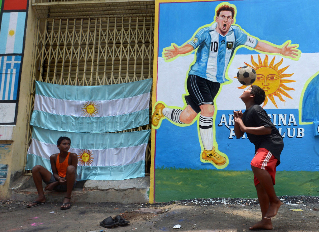 . An Indian boy heads a football in front of graffiti of Argentine soccer player Lionel Messi at the roadside in Kolkata on June 10, 2014. Football fans in the eastern Indian city are gearing up for the upcoming Brazil FIFA World Cup 2014 and decorating their clubs with football-related paraphernalia. AFP PHOTO/ Dibyangshu SARKAR/AFP/Getty Images
