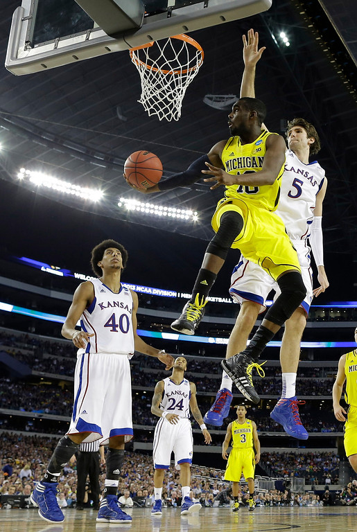 . Michigan\'s Tim Hardaway Jr. (10) drives past Kansas\' Jeff Withey (5) during the second half of a regional semifinal game in the NCAA college basketball tournament, Friday, March 29, 2013, in Arlington, Texas. (AP Photo/David J. Phillip)