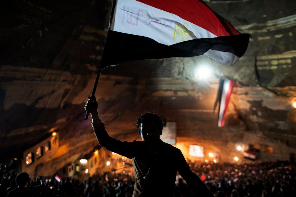 Description of . An Egyptian flag is waved as thousands of Egyptian Copts attend a Mass celebration in the Cave Cathedral or St Sama'ans in the Manshiet Nasser district of Cairo on December 13, 2012 where they prayed for Egypt ahead of the disputed referendum on the new draft Constitution slated for Saturday December 15th. MARCO LONGARI/AFP/Getty Images