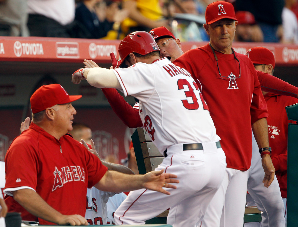 . Los Angeles Angels\' Josh Hamilton (32) gets congratulations from the bench after hitting a two-run home run against the Seattle Mariners in the first inning during a baseball game Tuesday, May 21, 2013 in Anaheim.    (AP Photo/Alex Gallardo)