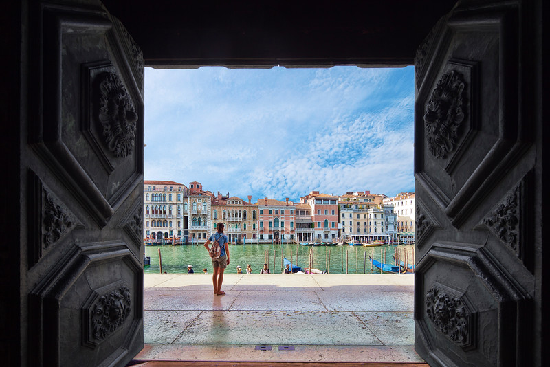A girl looking at the Grand Canal framed by the door of La Salute church, Dorsoduro, Venice, Italy