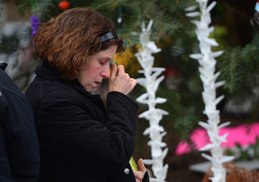 . People reflect at a makeshift shrine to the victims of an elementary school shooting in Newtown, Connecticut, December 17, 2012.  Funerals began Monday in the little Connecticut town of Newtown after the school massacre that took the lives of 20 small children and six staff, triggering new momentum for a change to America\'s gun culture. The first burials, held under raw, wet skies, were for two six-year-old boys who were among those shot in Sandy Hook Elementary School. On Tuesday, the first of the girls, also aged six, was due to be laid to rest. There were no Monday classes at all across Newtown, and the blood-soaked elementary school was to remain a closed crime scene indefinitely, authorities said.    AFP PHOTO/Emmanuel  DUNAND/AFP/Getty Images