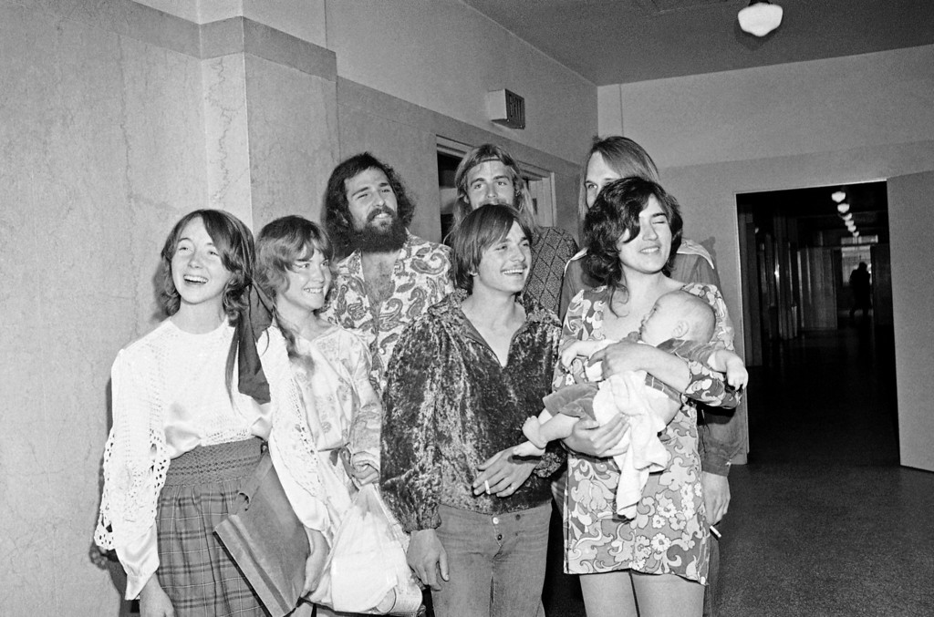 """. Members of Charles Manson\'s \""""family\"""" congregate in Los Angeles Hall of Justice, Feb. 24, 1970,  for arraignment of Patricia Krenwinkel, a defendant in the Sharon Tate murder case. None of these is accused.  From left: Lynette \""""Squeaky\"""" Fromme, Sandra Good, Mark Ross, Paul Watkins and  Catherine \""""Gypsy\"""" Share holding Catherine Good\'s son Ivan.  Two men partially hidden in back are unidentified. (AP Photo/Wally Fong)"""