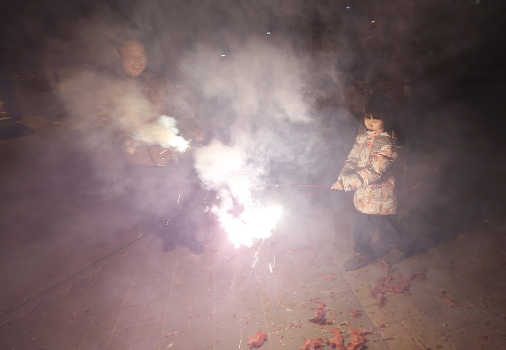 . Smoke surrounds residents holding sparklers outside their homes minutes after midnight in Beijing, China, 31 January 2014. The Lunar New Year ushers in the Year of the Horse on 31 January, and officially starts the Spring Festival in China.  EPA/ROLEX DELA PENA