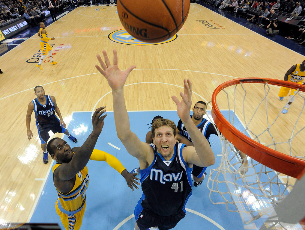 . Dallas Mavericks power forward Dirk Nowitzki (41) goes up for a rebound as Denver Nuggets center J.J. Hickson (7) looks on March 5, 2014 at Pepsi Center. The Denver Nuggets  defeated the Dallas Mavericks 115-110 (Photo by John Leyba/The Denver Post)