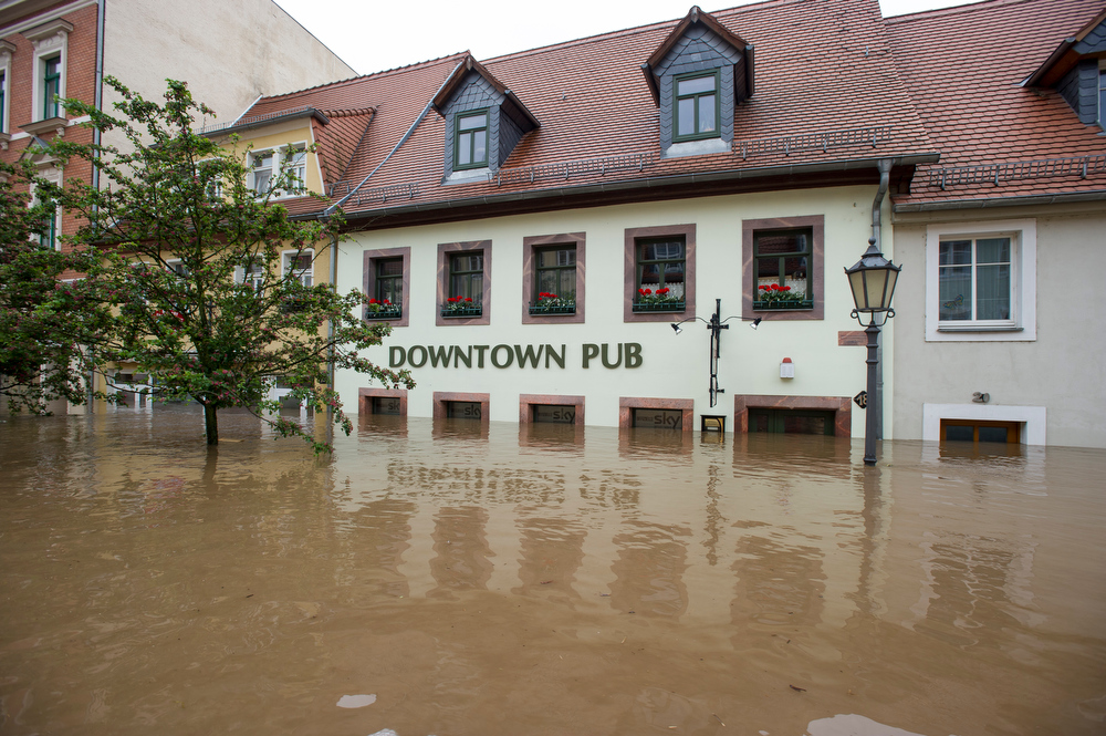 . Water fills the flooded city center in front of a pub on June 3, 2013 in Grimma, Germany. Heavy rains are pounding southern and eastern Germany, causing wide-spread flooding and ruining crops. At least two people are missing and feared dead in what is evolving into the most serious flood levels since the so-called 100-year flood of 2002. Portions of Austria and the Czech Republic are also inundated. (Photo by Jens Schlueter/Getty Images)