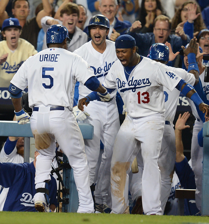 . The Dodgers\'  Juan Uribe is congratulated by Andre Ethier and Hanley Ramirez after his bottom of the 8th 2 run homer against the Atlanta Braves during game 4 of the NLDS at Dodger Stadium Monday, October 7, 2013. The Dodgers beat the Braves 4-3.(Photo by Hans Gutknecht/Los Angeles Daily News)