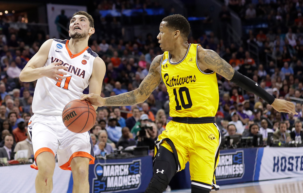 . UMBC\'s Jairus Lyles (10) knocks the ball from Virginia\'s Ty Jerome (11) during the first half of a first-round game in the NCAA men\'s college basketball tournament in Charlotte, N.C., Friday, March 16, 2018. (AP Photo/Gerry Broome)