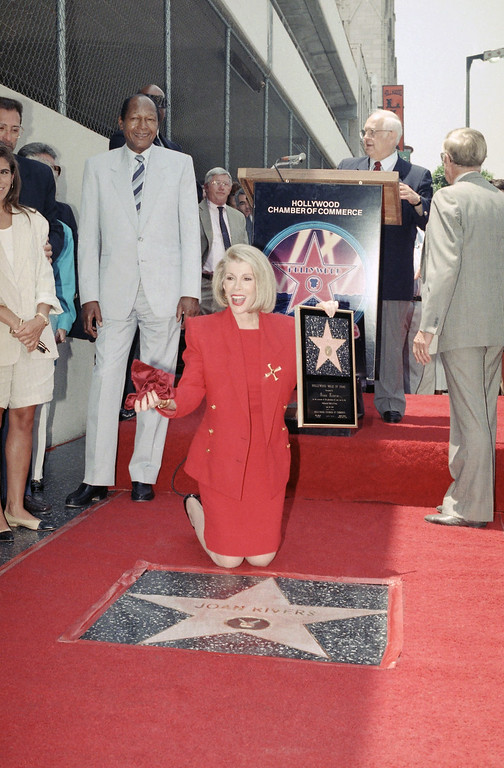 . Comedienne Joan Rivers poses next to her new star on the Hollywood Walk of Fame in Hollywood, Los Angeles on Wednesday, July 26, 1989. She was honored for her contributions to the world of entertainment, specifically television. (AP Photo/Doug Sheridan)