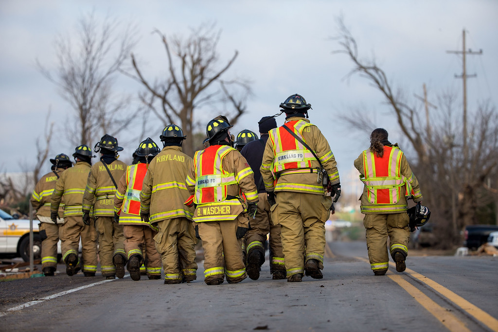 . The Kirkland Fire Department walks along IL-72 while search through the town for unaccounted people the morning after a tornado swept through the town on April 10, 2015 in Fairdale, Illinois. According to reports, 11 people were injured and one person was killed when tornadoes and thunderstorms passed through the northwestern suburbs of Chicago. (Photo by Jon Durr/Getty Images)