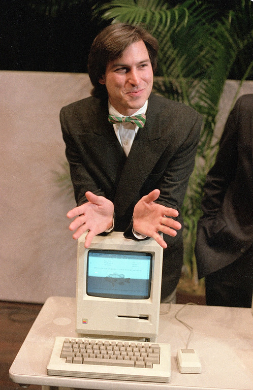 """. Steven Jobs, chairman of the board of Apple Computer, leans on the new """"Macintosh"""" personal comptuer following a shareholder\'s meeting Jan. 24, 1984 in Cupertino, Ca.  The Macintosh, priced at $2,495, is challenging IBM in the personal computer market. (AP Photo/Paul Sakuma)"""
