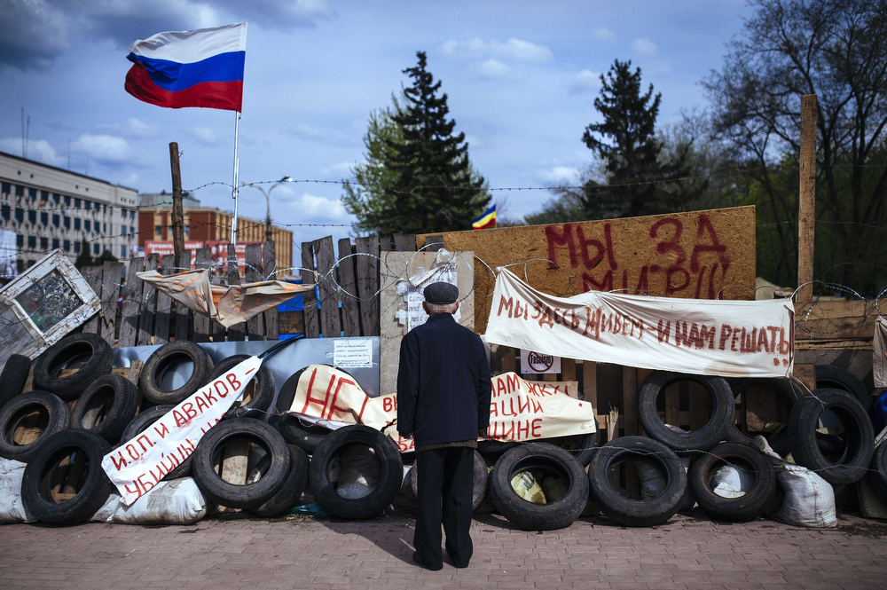 """. An elderly man stands next a barricade  near the secret service building in the eastern Ukrainian city of Lugansk on April 22, 2014. US Vice President Joe Biden warned Russia of isolation if it continues to try to \""""pull Ukraine apart\"""" and pledged Washington\'s strong support for Kiev\'s leaders, as a Cold War-style confrontation over the former Soviet republic ratcheted up.  (DIMITAR DILKOFF/AFP/Getty Images)"""