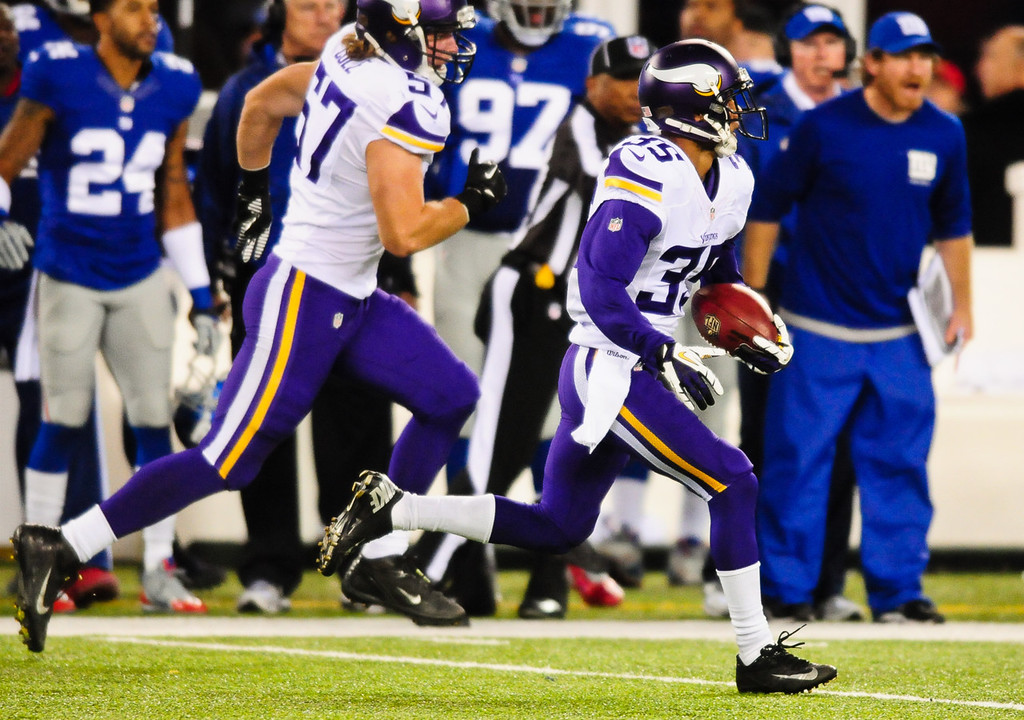 . Vikings cornerback Marcus Sherels returns a punt for 86 yards and a touchdown in the first quarter against the Giants. At left is Vikings linebacker Audie Cole. (Pioneer Press: Ben Garvin)