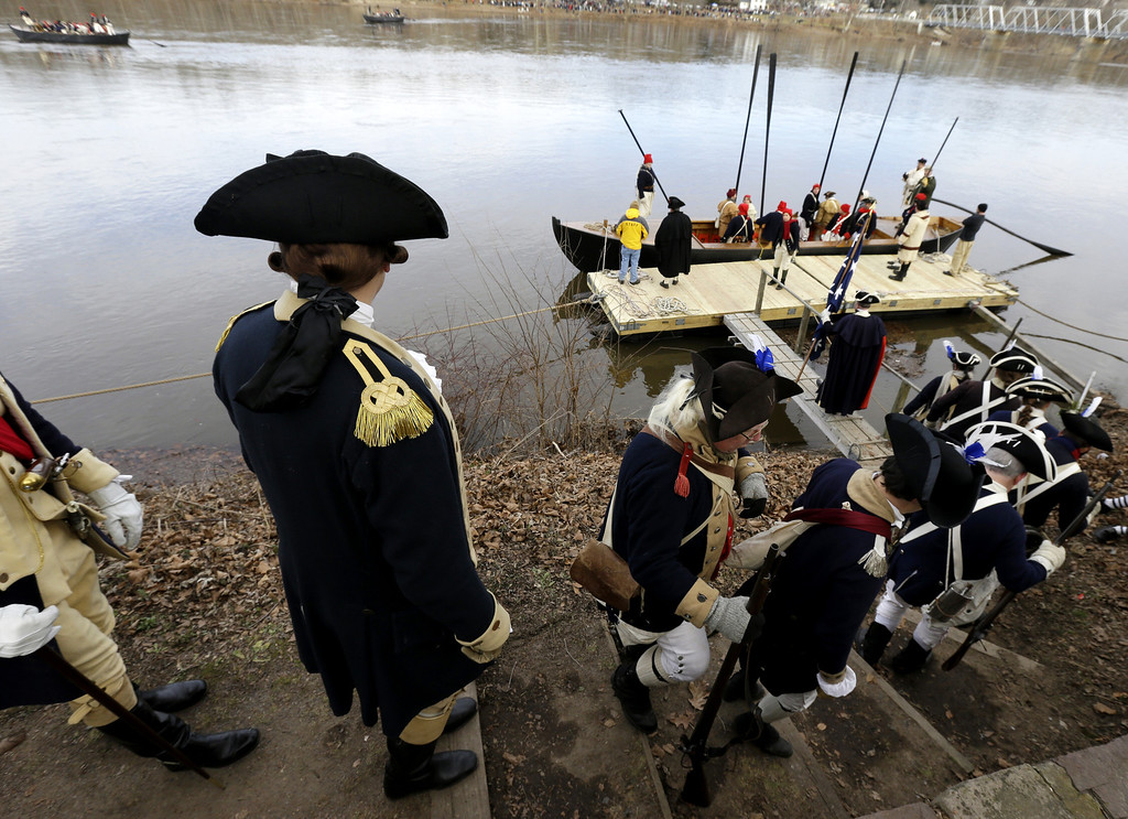 . John Godzieba, left, playing the role of Gen. George Washington, walks behind his troops onto a dock during the 61st annual re-enactment of Washington\'s daring Christmas 1776 crossing of the river, the trek that turned the tide of the Revolutionary War, in Washington Crossing, N.J. During the crossing 237 years ago, boats ferried 2,400 soldiers, 200 horses and 18 cannons across the river, and the troops marched eight miles downriver before battling Hessian mercenaries in the streets of Trenton. (AP Photo/Julio Cortez)