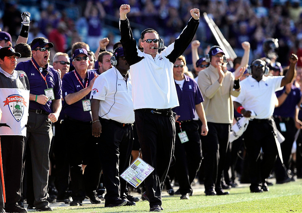 Description of . Northwestern head coach Pat Fitzgerald celebrates a first down in the closing seconds of the second half of the Gator Bowl NCAA college football game against Mississippi State, Tuesday, Jan. 1, 2013 in Jacksonville, Fla. Northwestern won  34-20. (AP Photo/Stephen Morton)