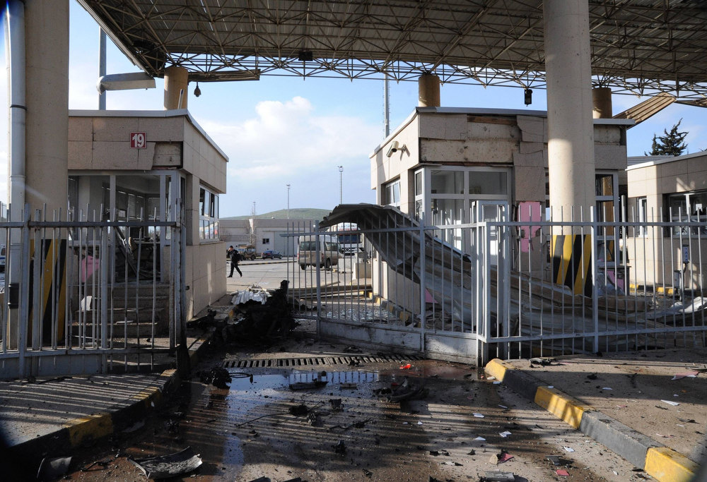 Description of . A man walks past a damaged gate after an explosion at Cilvegozu border gate on the Turkish-Syrian border in Hatay province February 11, 2013, in this picture taken by Anadolu Agency. A car exploded at the border crossing near the Turkish town of Reyhanli on Monday, killing at least seven people and wounding dozens more, officials said.       REUTERS/Cem Genco/Anadolu Agency