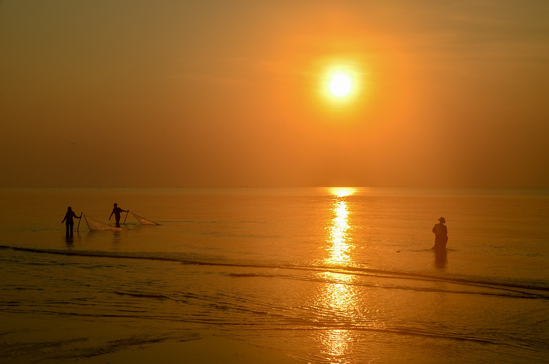 Tropical sunrise seascape with sun water reflection and fishermen silhouettes, Thailand.